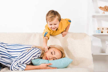 smiling little boy touching mother sleeping on sofa at home