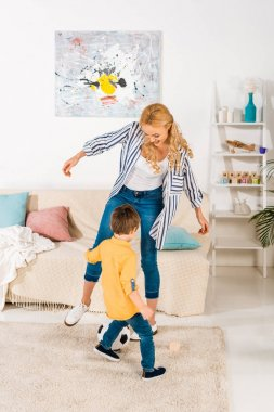 cheerful mother and little son playing with soccer ball at home