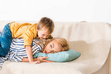 cute little smiling boy hugging mother sleeping on sofa at home