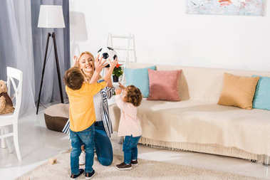 happy mother and adorable little kids holding soccer ball at home
