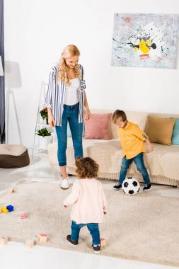 Cheerful mother and cute little children playing with soccer ball at home stock vector