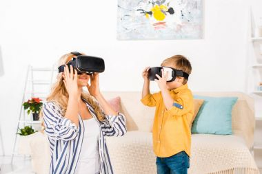 beautiful happy mother and son using virtual reality headsets at home