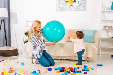 smiling mother and adorable little daughter playing with fit ball and colorful blocks at home