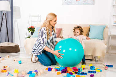 happy mother and cute little daughter playing with fit ball and colorful blocks at home