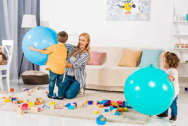happy mother and kids playing with fitness balls and colorful blocks at home