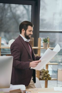handsome architect looking at blueprint in modern office