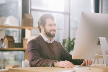 Handsome architect working with computer in office with backlit stock vector