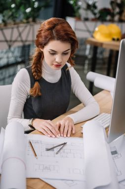young beautiful businesswoman sitting  looking at papers on table