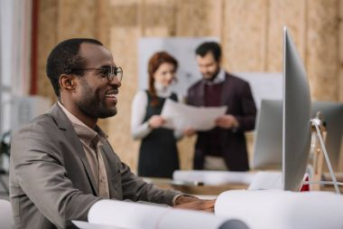 happy african american architect working with computer at modern office while his colleagues discussing contract