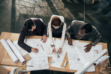 High angle view of team of architects working together with plans at office stock vector