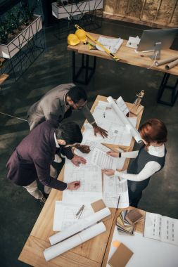 high angle view of team of architects working with architectural plans at office