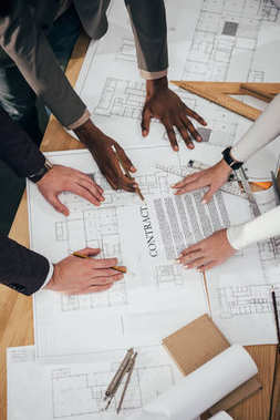 Cropped shot of team of architects working together with contract and building plans stock vector