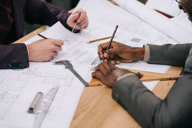 cropped shot of architects drawing architectural plans together