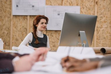 young female architect working with computer at office while colleagues drawong plans on foreground