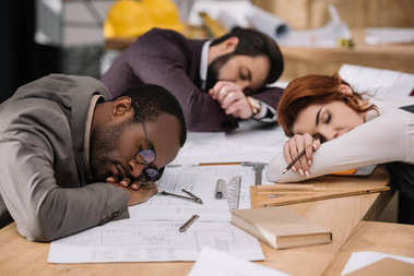 multiethnic overworked team of architects sleeping at office