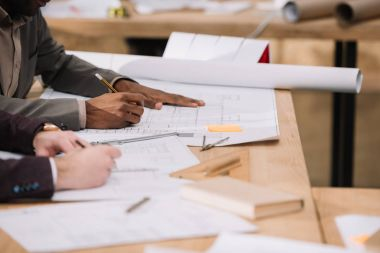 cropped shot of architects drawing building plans together at office