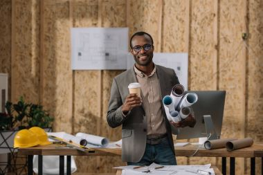 smilign african american architect with coffee to go and rolled blueprints at workplace