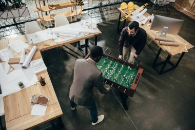 high angle view of young architects playing table football in office full of building plans