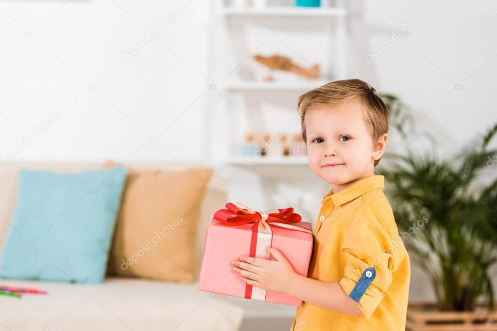 side view of little boy holding wrapped present in hands