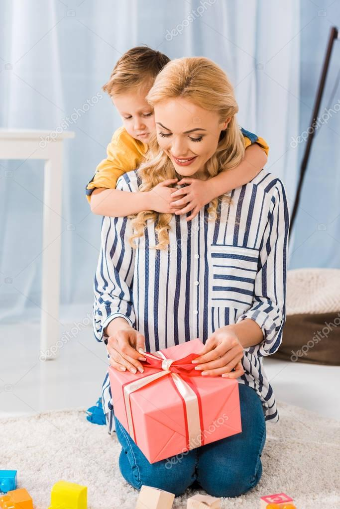 little son hugging mother with wrapped gift in hands