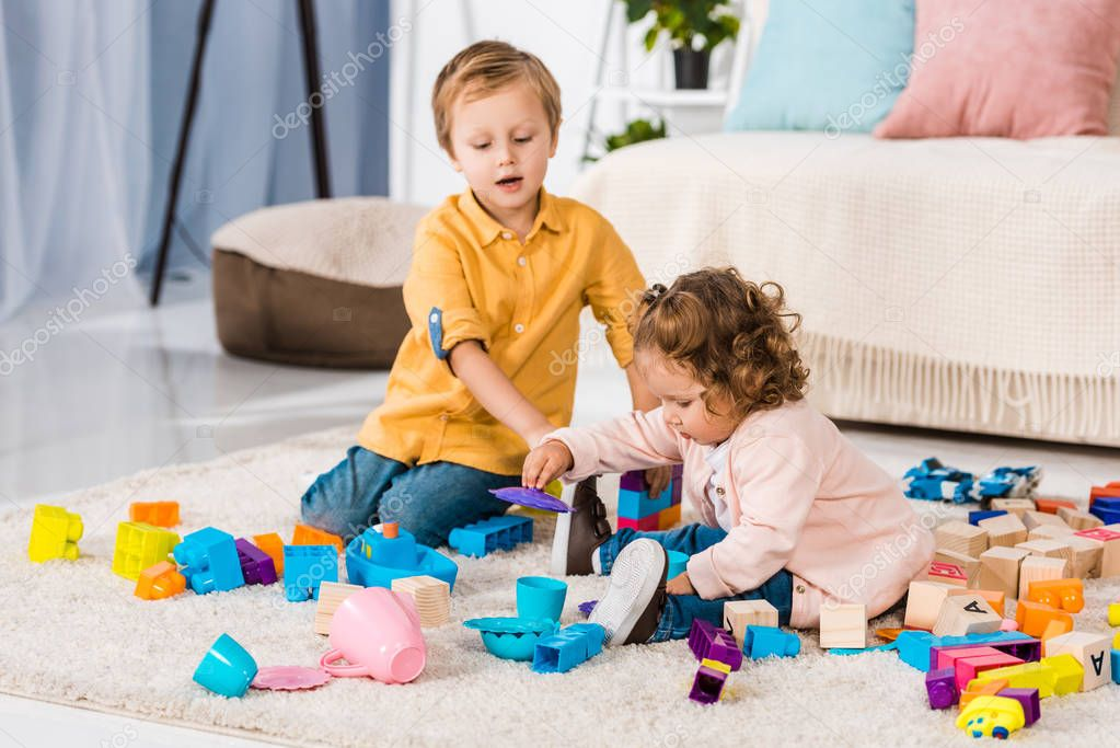 adorable siblings playing with plastic blocks on floor