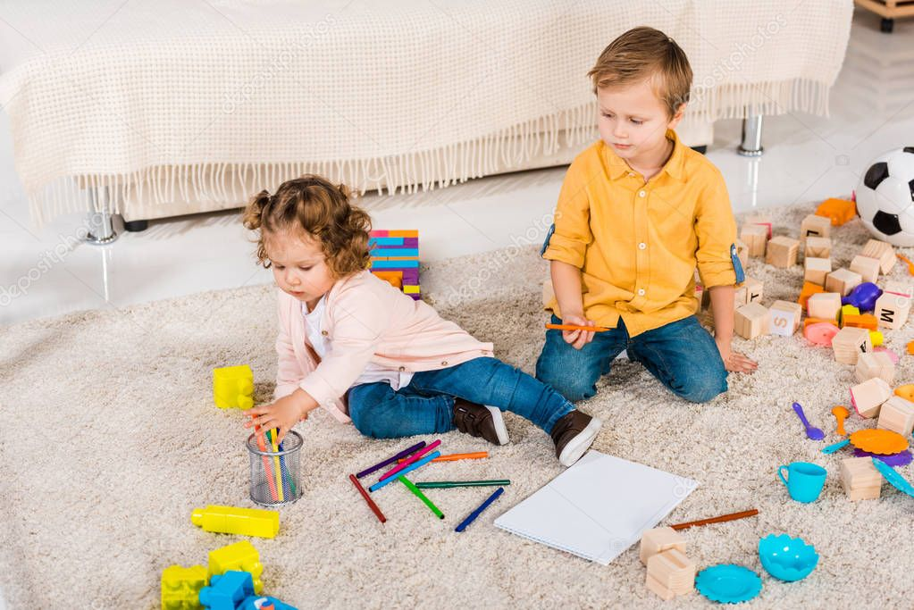 adorable siblings playing on a floor with colored pencils