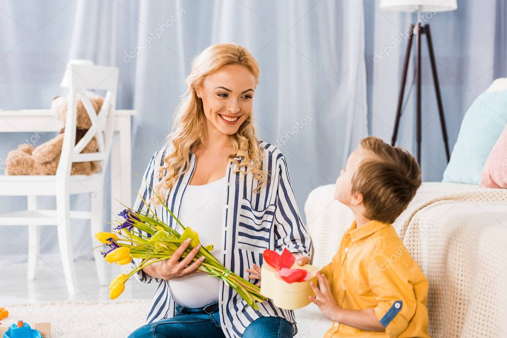adorable little boy presenting to happy pregnant mother tulip flowers and heart shaped gift box