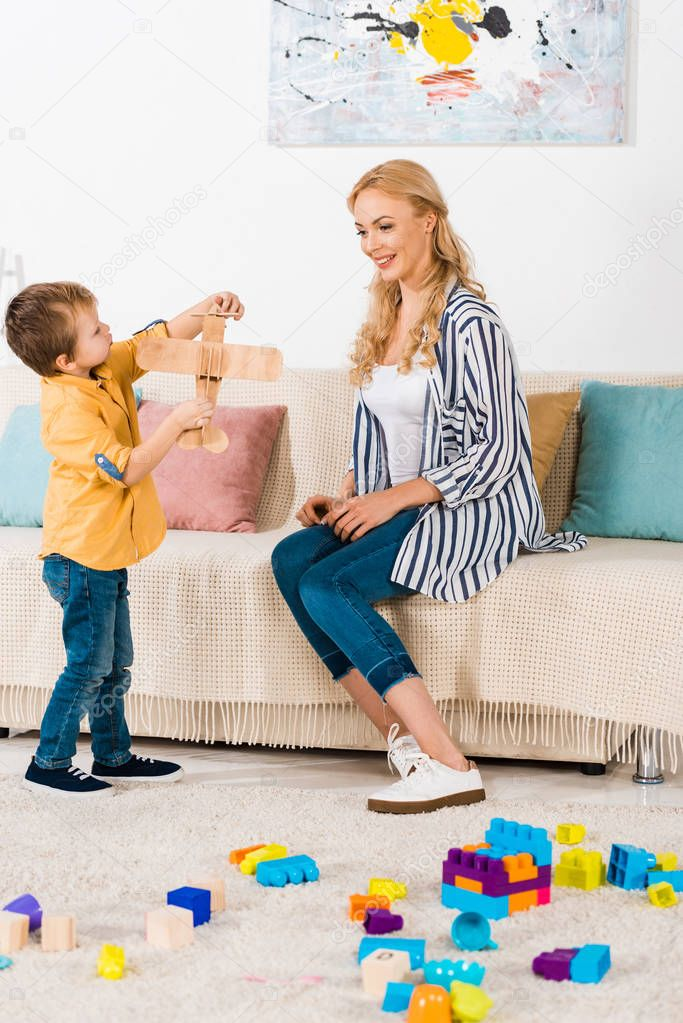 happy mother sitting on sofa and looking at cute little son playing with toy plane at home