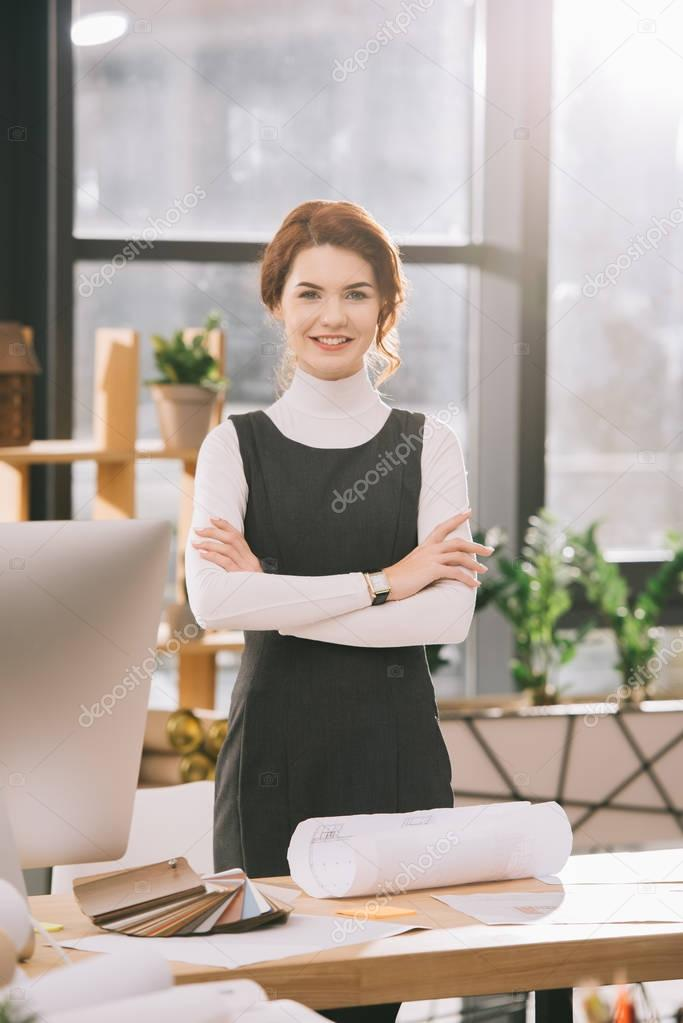 Female architect with crossed arms standing at workplace with blueprints