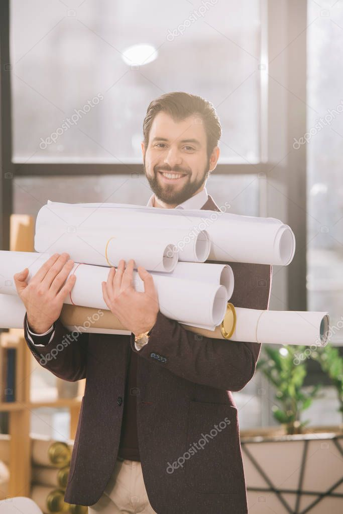 smiling architect holding pile of blueprints in modern office with backlit