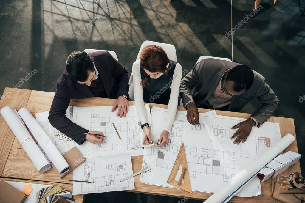 high angle view of team of architects working together with plans at office