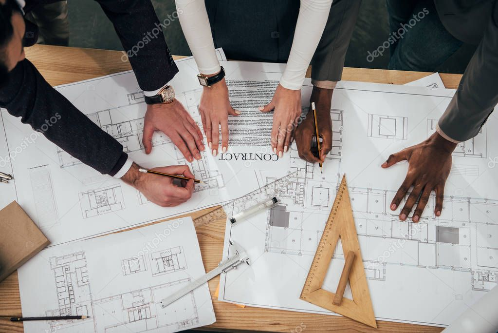 cropped shot of team of architects with building contract and plans