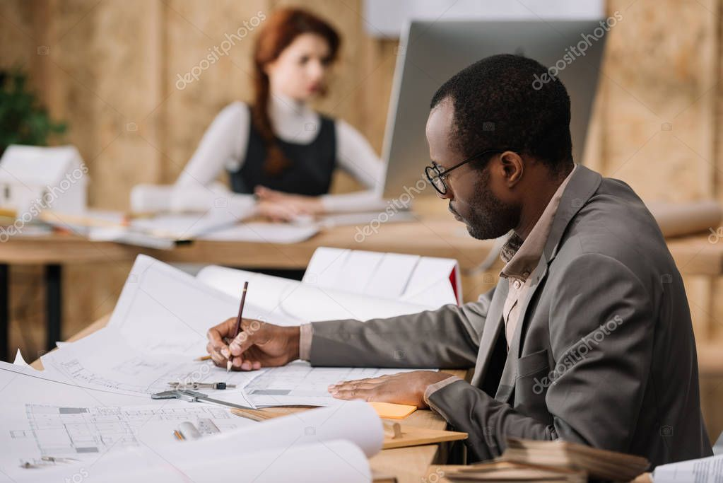 Handsome african american architect drawing building plans while his colleague working with computer