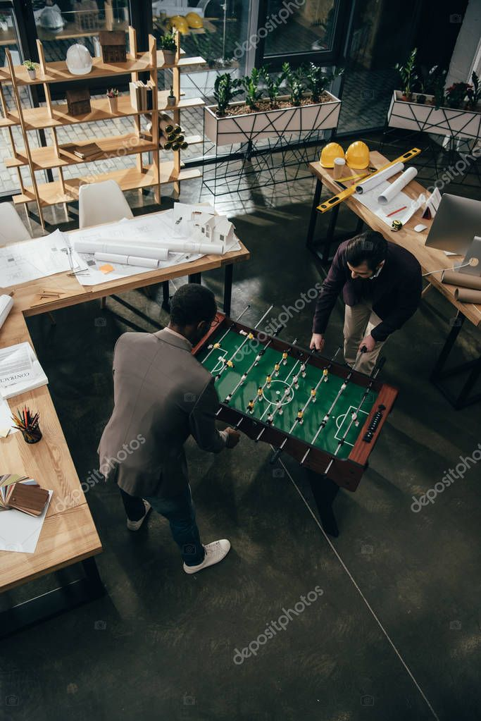 high angle view of multiethnic architects playing table football in office