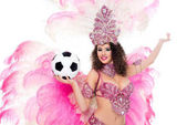 Photo woman in carnival costume holding football ball in hand and looking at camera, isolated on white