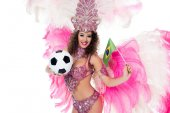 Fotografie smiling woman in carnival costume holding football ball and brazilian flag while looking at camera, isolated on white