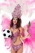 smiling woman in carnival costume holding football ball and brazilian flag, isolated on white