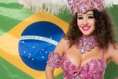 Cheerful woman in carnival costume with pink feathers on Brasil flag background