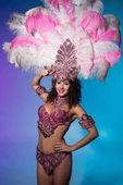 Fotografia Donna brillante in costume di carnevale con le piume rosa pose emotivamente su priorità bassa blu