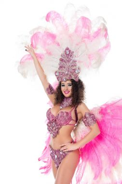 cheerful woman posing in carnival costume with pink feathers, isolated on white