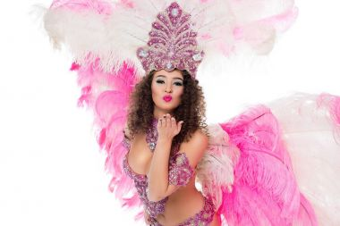 woman posing in carnival costume with pink feathers blowing kiss, isolated on white