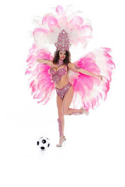 woman in carnival costume about kick football ball, isolated on white