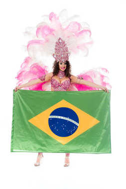 Happy young woman in carnival costume with pink feathers holds large flag of Brasil isolated on white stock vector