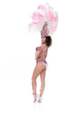Bright woman in carnival costume with pink feathers looks into camera isolated on white