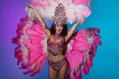 Veselá žena v karnevalový kostým růžové peří zvyšování rukou izolované na modrém pozadí