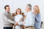 Fotografie Couple of middle aged man and woman greeting their friends as guests and shaking hands
