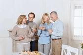Glückliche Freunde jubeln stehend gegen Tisch