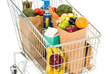 Close-up view of full grocery bags in shopping trolley isolated on white stock vector