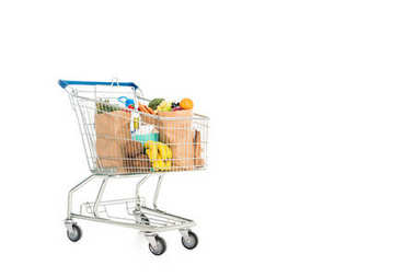 paper bags full of fruits and vegetables in shopping trolley isolated on white
