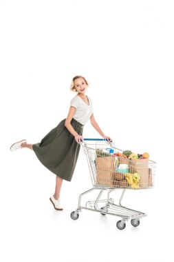 happy young woman standing with shopping trolley and smiling at camera isolated on white